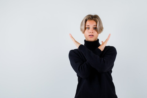 Ragazzo adolescente in maglione nero che mostra il gesto di arresto con le braccia incrociate e sembra sorpreso, vista frontale.