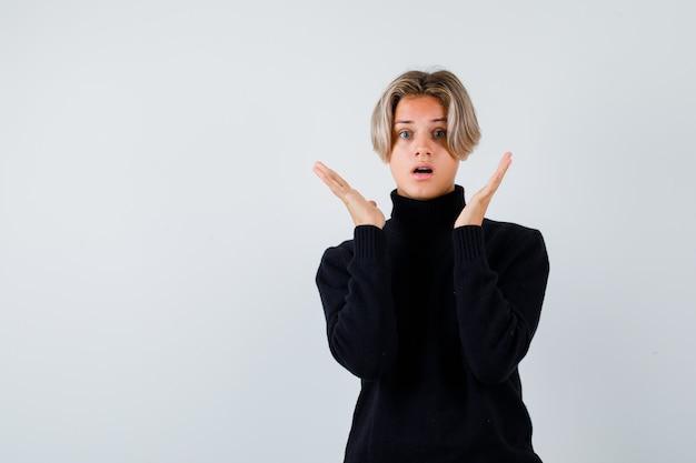 Ragazzo teenager in maglione nero che spande le palme e che sembra scioccato, vista frontale.