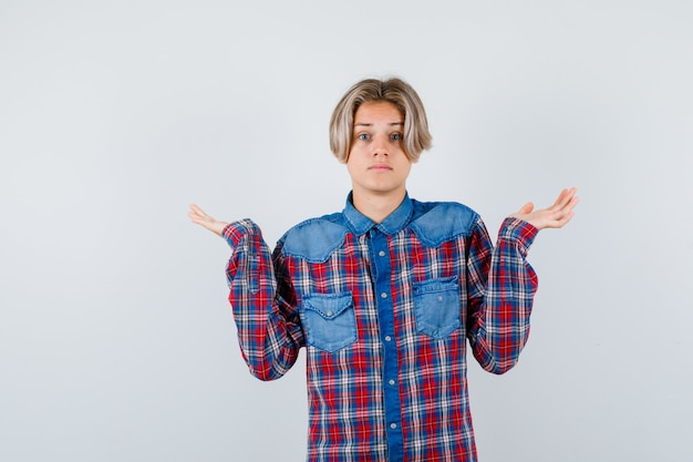 Ragazzo adolescente in camicia a scacchi che mostra gesto impotente e sembra ansioso, vista frontale.