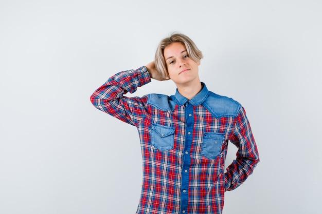 Ragazzo adolescente in camicia a scacchi con la mano dietro la testa e guardando rilassato, vista frontale.