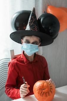 Ragazzo adolescente in costume e maschere per il viso per proteggersi da covid-19 che disegna una zucca per la celebrazione di halloween