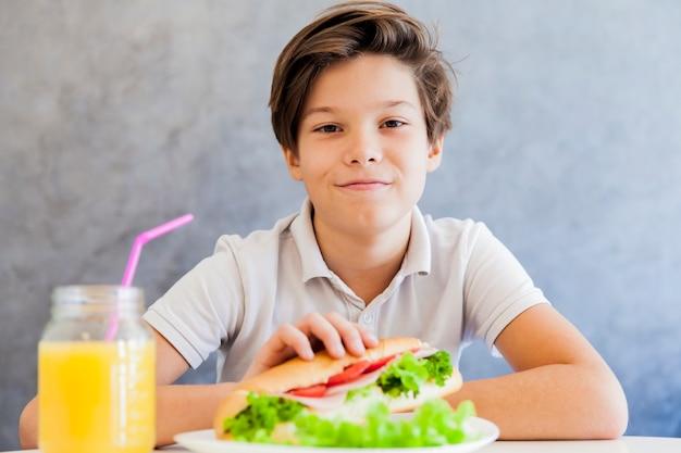 Ragazzo teenager che mangia prima colazione a casa