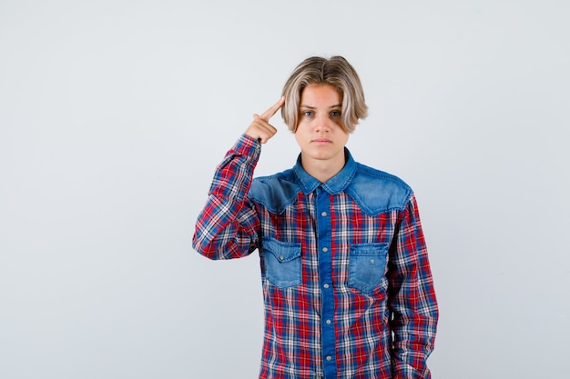 Ragazzo teenager che tiene il dito sulla testa in camicia a scacchi e sembra deluso. vista frontale.