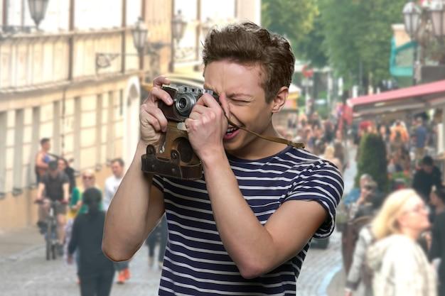 Il ragazzo adolescente sta scattando una foto dell'architettura europea. folle di persone ed edifici sullo sfondo.
