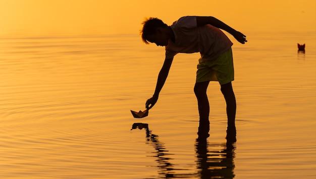 Ragazzo teenager che lancia navi di carta sull'acqua. navi galleggianti in lontananza