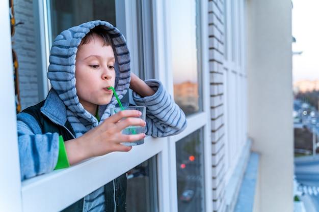 Ragazzo adolescente che guarda fuori dalla finestra dell'appartamento