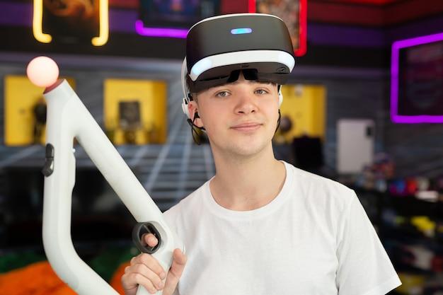 Adolescente, ragazzo che gioca su una console per videogiochi, giocatore emotivo che spara a un gioco usando un controller di pistola in un club di gioco. vr