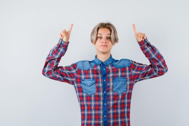 Ragazzo teenager che indica in su in camicia a quadretti e che sembra sicuro di sé, vista frontale.