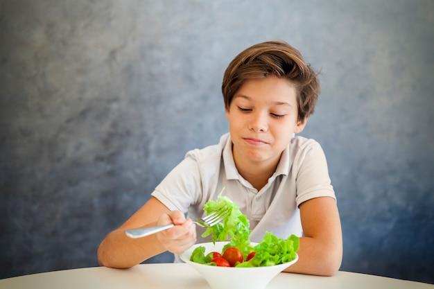 Ragazzo adolescente si rifiuta di mangiare insalata