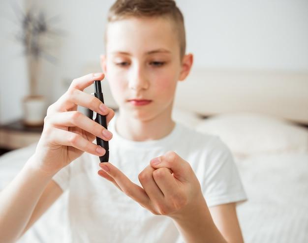 Il ragazzo teenager prende un campione di sangue per il diabete con la penna della lancetta. salute, medicina e concetto diabetico