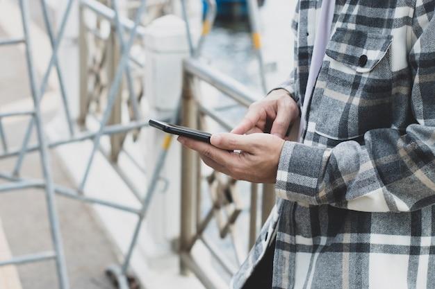 Ragazzo teenager che utilizza il dispositivo dello smartphone per internet in linea di tecnologia della rete; l'uomo usa il cellulare nel parco pubblico