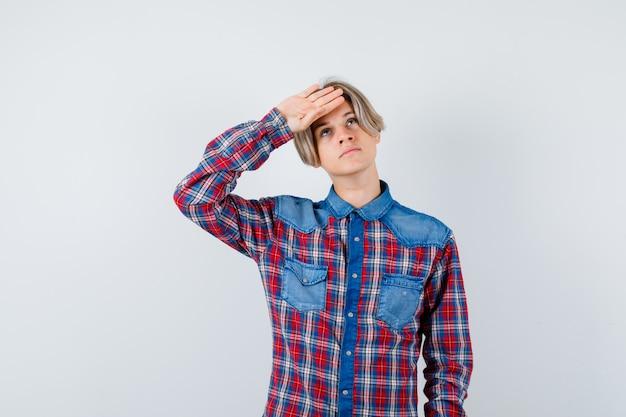 Ragazzo teenager con la mano sulla fronte in camicia a scacchi e guardando pensieroso, vista frontale.