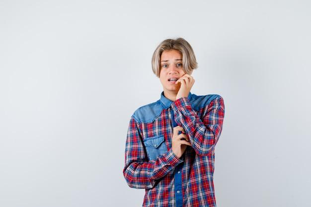 Ragazzo teenager con la mano vicino alla bocca in camicia a scacchi e sembra spaventato. vista frontale.