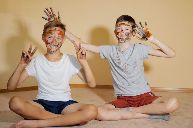 Ragazzi adolescenti seduti sul pavimento con le mani e i volti in vernici colorate che guardano la telecamera