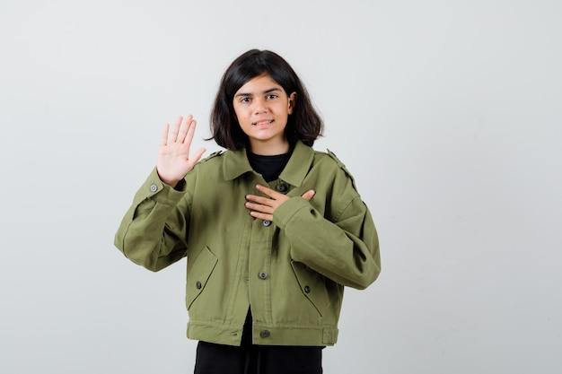 Ragazza teenager in giacca verde militare che tiene la mano sul petto, mostrando il palmo e guardando allegra, vista frontale.