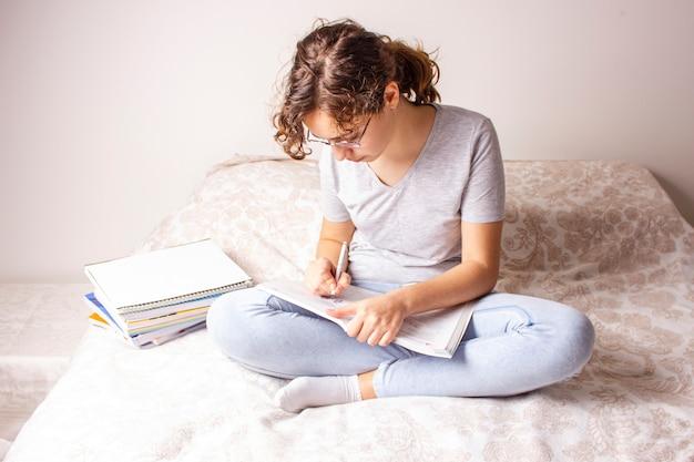 Ragazza teenager sul letto che studia a casa a causa della quarantena