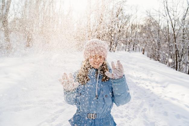 Una ragazza adolescente con un cappotto blu mostra i guanti con la neve bloccata mentre gioca e la neve che vola dentro di lei.