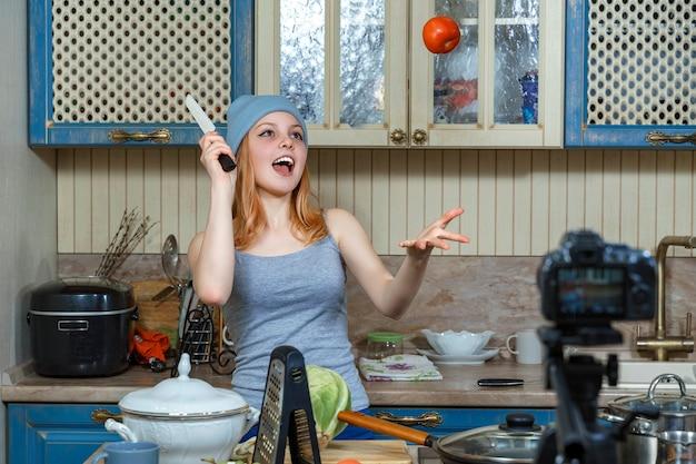 Ragazza teenager in cappello blu e t-shirt scrive video per blog di cucina e fa trucchi con i pomodori.