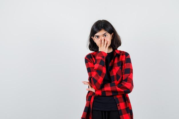 Ragazza teenager in camicia casual che copre la bocca con le mani e sembra scioccata, vista frontale.