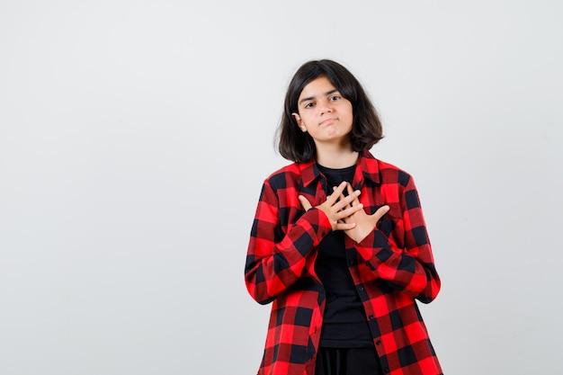 Ragazza teenager in camicia casual che si tiene per mano sul petto e che sembra pensierosa, vista frontale.