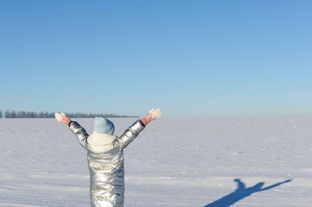 La ragazza teenager gode del periodo invernale, stando in piedi sul campo di neve alzato le mani al cielo blu.