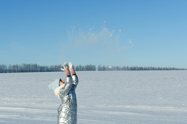La ragazza teenager gode del periodo invernale, lanciando la neve al cielo blu.