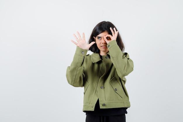 Ragazza teenager in giacca verde che mostra gesto ok e sembra curiosa, vista frontale.