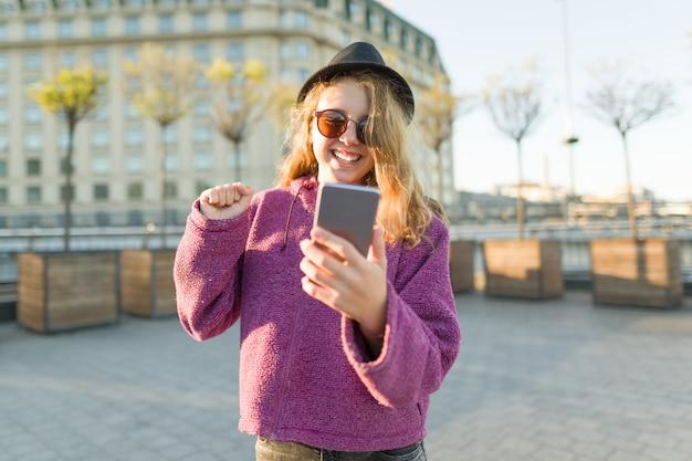 Pantaloni a vita bassa teenager della ragazza in cappello e vetri con il telefono cellulare
