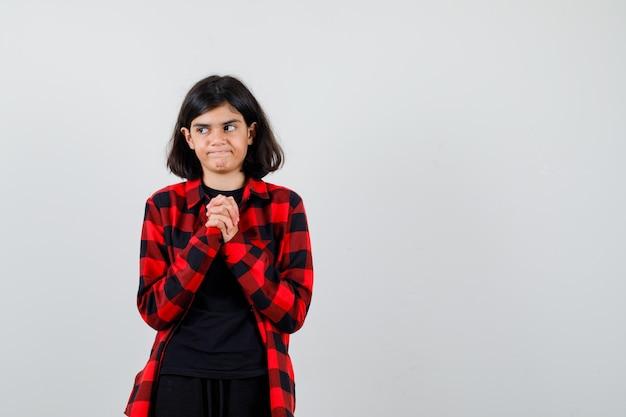 Ragazza teenager che tiene le dita intrecciate sul petto in t-shirt, camicia a scacchi e sembra insoddisfatta, vista frontale.