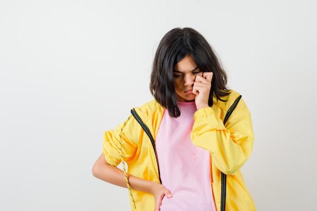 Ragazza teenager che tiene la mano sulla guancia e sulla vita in tuta gialla, t-shirt e sembra premurosa, vista frontale.