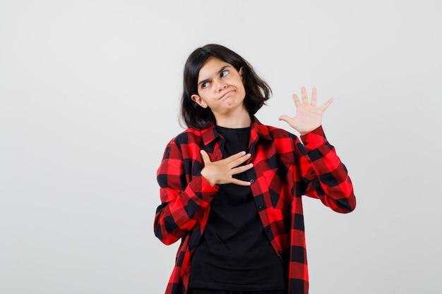 Ragazza teenager che tiene la mano sul petto mentre mostra il palmo in maglietta, camicia a scacchi e sembra insoddisfatta. vista frontale.