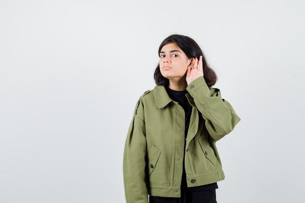 Ragazza teenager che tiene la mano dietro l'orecchio in giacca verde e sembra seria, vista frontale.