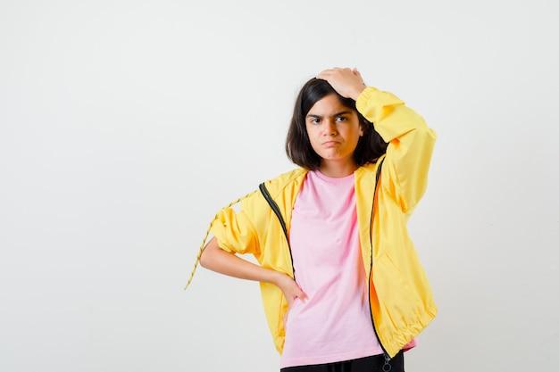 Ragazza teenager che tiene la mano sulla testa e sulla vita in tuta gialla, t-shirt e sembra sconvolta, vista frontale.