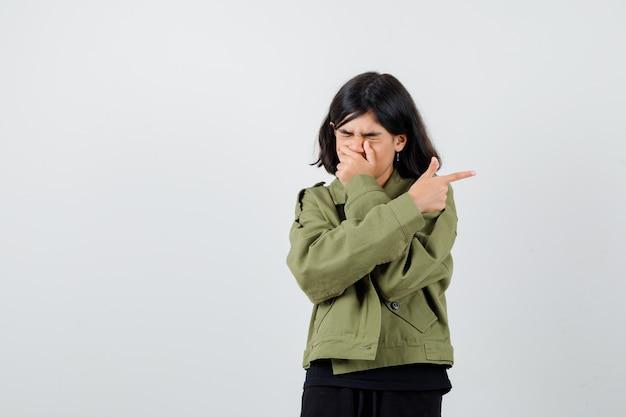 Ragazza teenager che tiene la mano sulla bocca mentre indica il lato destro in maglietta, giacca e sembra addolorata. vista frontale.
