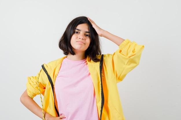 Ragazza teenager che tiene il palmo sulla testa in tuta gialla, t-shirt e guardando pensieroso, vista frontale.