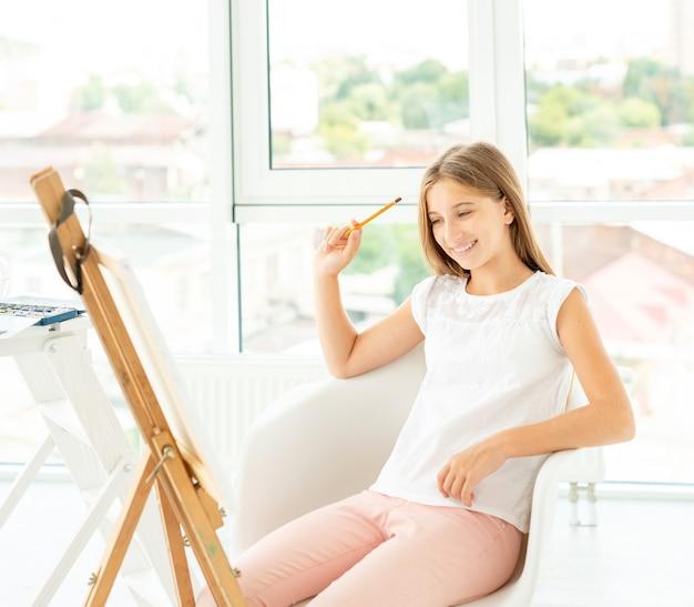La ragazza teenager sta disegnando il grafico con la matita