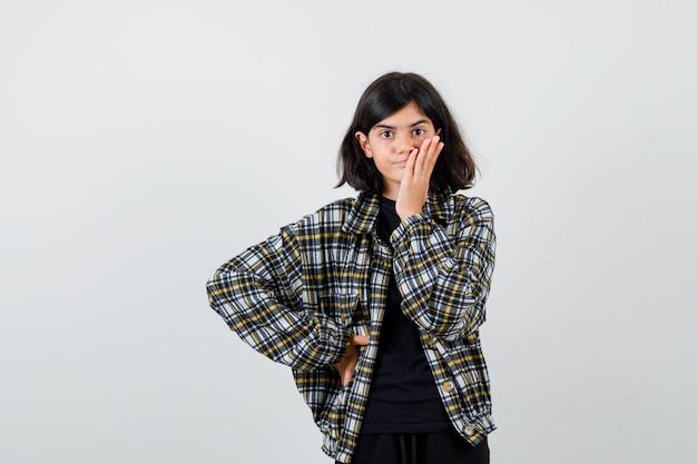 Ragazza teenager che tiene la mano sul viso, tenendo la mano sulla vita in camicia casual e sembra sconvolta, vista frontale.