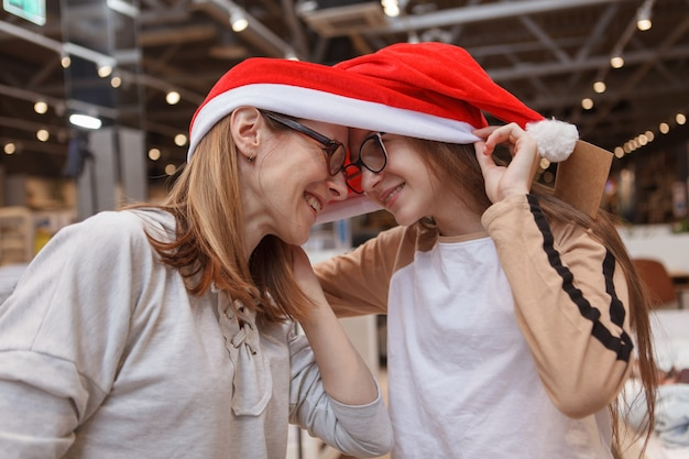 Ragazza teenager che ride, toccando la fronte con sua madre, indossando il cappello di babbo natale insieme