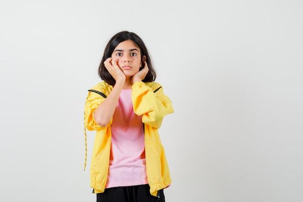 Ragazza teenager che si appoggia il mento sulle mani in tuta gialla, t-shirt e sembra sorpresa, vista frontale.