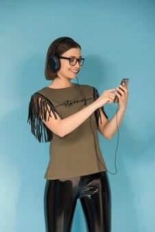 Ragazza teenager che ascolta la musica sul suo telefono cellulare con le cuffie