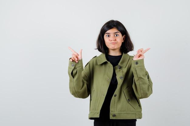 Ragazza teenager che indica a destra ea sinistra in giacca verde militare e sembra indecisa, vista frontale.