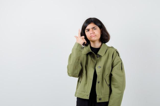 Ragazza teenager che indica in su in giacca verde militare e che sembra triste, vista frontale.