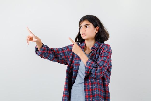 Teen ragazza rivolta verso l'alto, in piedi lateralmente in camicia a scacchi e sembra spaventata.