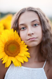 Fronte teenager del ritratto della ragazza nel giacimento dei girasoli.
