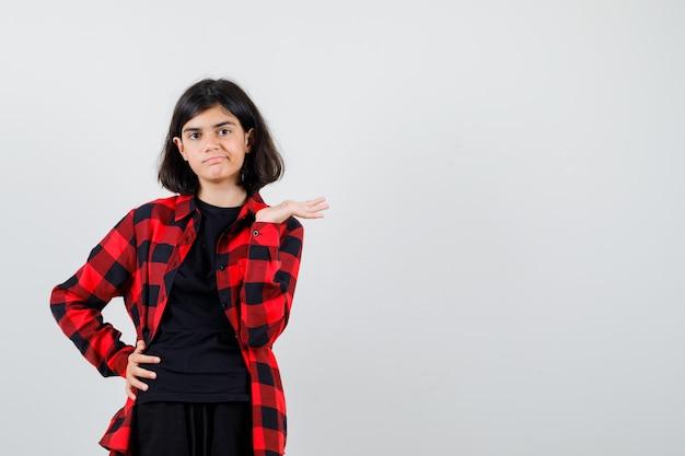 Ragazza teenager che finge di tenere o mostrare qualcosa in maglietta, camicia a scacchi e sembra insoddisfatta. vista frontale.