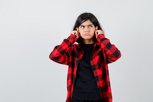 Ragazza teenager che tira giù i suoi lobi delle orecchie in maglietta, camicia a scacchi e guardando dispettoso, vista frontale.