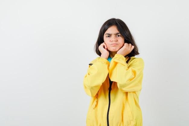 Ragazza teenager che tira giù i suoi lobi delle orecchie in giacca gialla e sembra insoddisfatta, vista frontale.