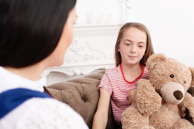 Ragazza teenager alla reception presso lo psicoterapeuta. sessione di psicoterapia per bambini