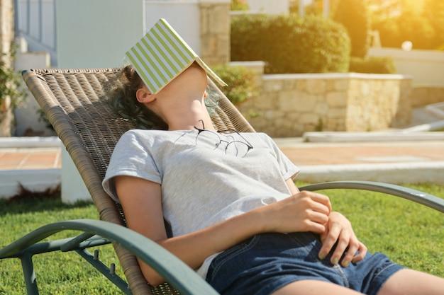 Ragazza teenager che riposa all'aperto seduto in poltrona sul prato verde, leggendo il libro e addormentarsi togliendosi gli occhiali, dormendo donna stanca