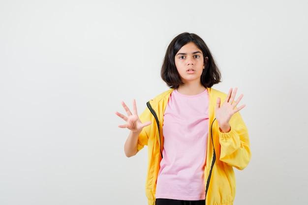 Ragazza teenager che mostra il gesto di arresto in tuta da ginnastica gialla, t-shirt e guardando sorpreso, vista frontale.